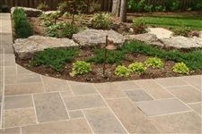 Flamboro Dark armourstone accents in a border garden