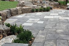 A single-high Flamboro Dark armourstone wall retaining a hill around a flagstone patio