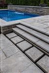 Eramosa Dark sandblasted coping with a custom sandblasted edge used as stair treads and stepping stones beside a pool