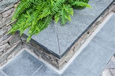 Imported Black Granite rockfaced natural stone coping on a fieldstone garden wall