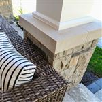 A custom-made beveled Indiana Limestone cap on a natural stone pillar