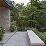 Indiana Limestone eased-edge coping on top of a natural stone seat wall at the front entrance of a home