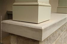A close-up of chamfered Indiana Limestone natural stone coping on top of a natural stone wall