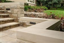 Custom-made eased-edge Indiana Limestone coping on top of a freestanding natural stone wall