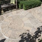 An Ebel Beige pebbletop square cut flagstone patio with a circular inlay