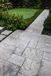 An Eramosa Dark sandblasted square cut flagstone patio and walkway beside a putting green