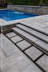 Eramosa Dark sandblasted square cut flagstone stepping stones and steps leading up to a raised poolside patio