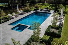A rectangular pool and hot tub surrounded by an Imported Black Granite square cut flagstone patio