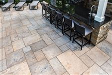 Deck chairs and an outdoor kitchen on a Wiarton Buff flamed square cut flagstone patio