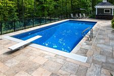 A Wiarton Buff flamed square cut flagstone patio around a rectangular pool