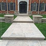 A terraced Wiarton Buff flamed square cut flagstone walkway leading to the front of a large home