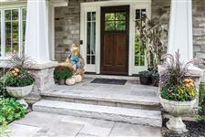 An Imported Grey step leading from a flagstone walkway to a front porch